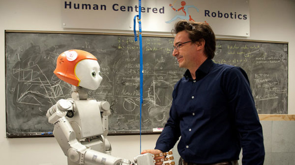 Assistant Professor Luis Sentis shakes hands with Dreamer the robot.