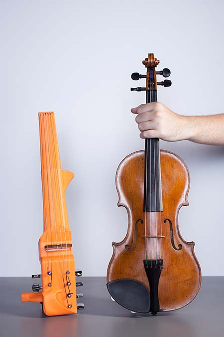 3D printed violin prototype next to a traditional violin.