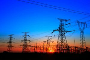 Towering power grids with the sun setting behind it/