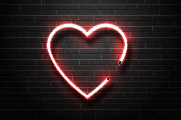 Faux neon Heart illuminated on brick wall