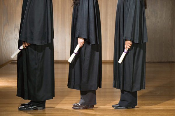 Three robed students standing with their diplomas in hand.