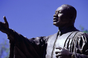 Statue of Martin Luther King Jr. reaching for the future against a clear blue sky.