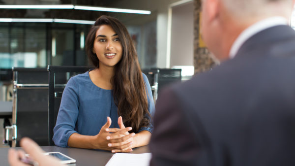 A young businesswoman sitting at table, talking to senior male manager and smiling in office.