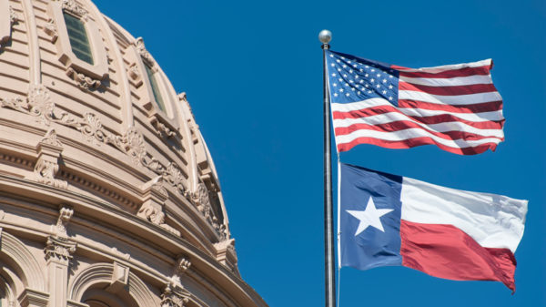 Texas Capitol Dome on the left with the American and Texas flags waving on the left.