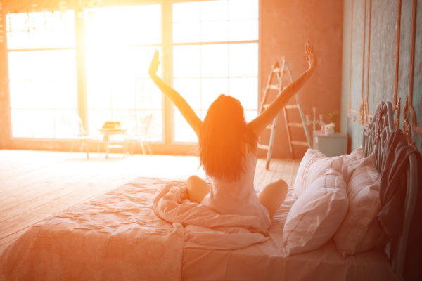 A woman in bed, stretching as the morning sun glows on her.