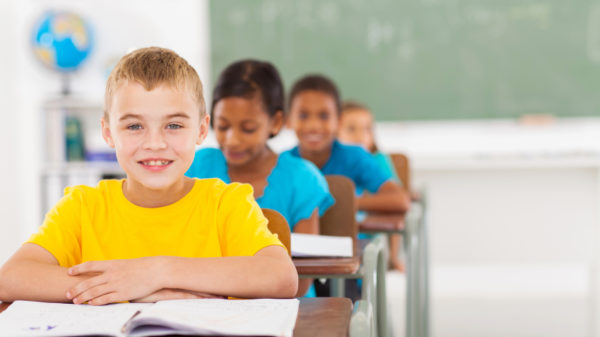 elementary schoolboy with classmates in classroom