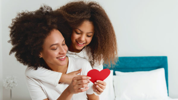 Mother and daughter enjoying on the bed, holding a heart