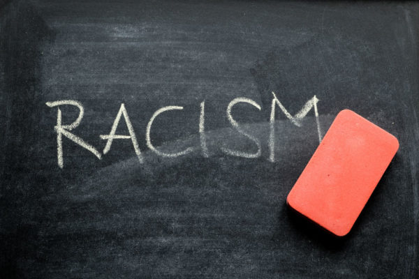 Racism written on chalkboard with an eraser.