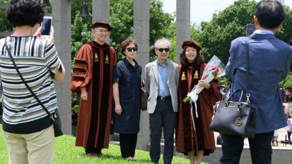Asian family posing for graduation photos.