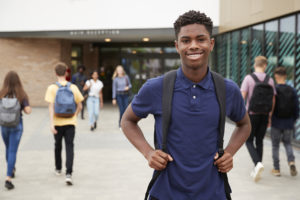 Portrait Of Smiling Male High School Student Outside College Building