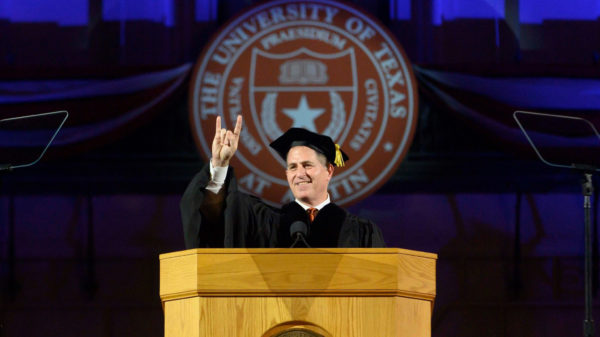Michael Dell doing hook'em horns sign.