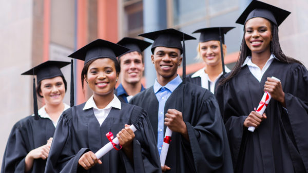 young graduates standing in front of university building on