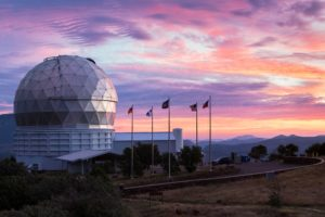 The dome of the Hobby-Eberly Telescope sits at left with a backdrop of a multi-colored West Texas sunset.