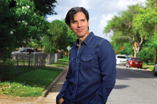 Oscar Cásares stands in a residential street.