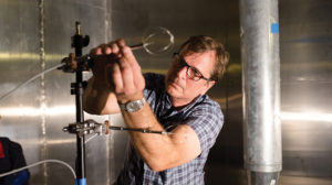 A man with glasses adjust some scientific measuring instruments attached to a rod.