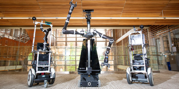 Two Building-Wide Intelligence Project (BWI) robots flank a robot from the Personal Autonomous Robotics Lab (PeARL), center, in the GDC at The University of Texas at Austin.
