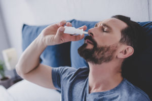 man spraying drops in his nose