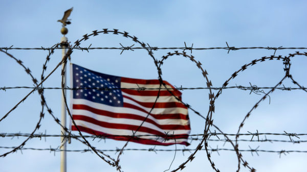 A U.S. flag blows in the wind behind razor wire
