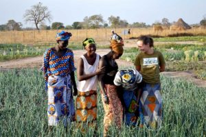 Student in the field with female farmers in Africa.