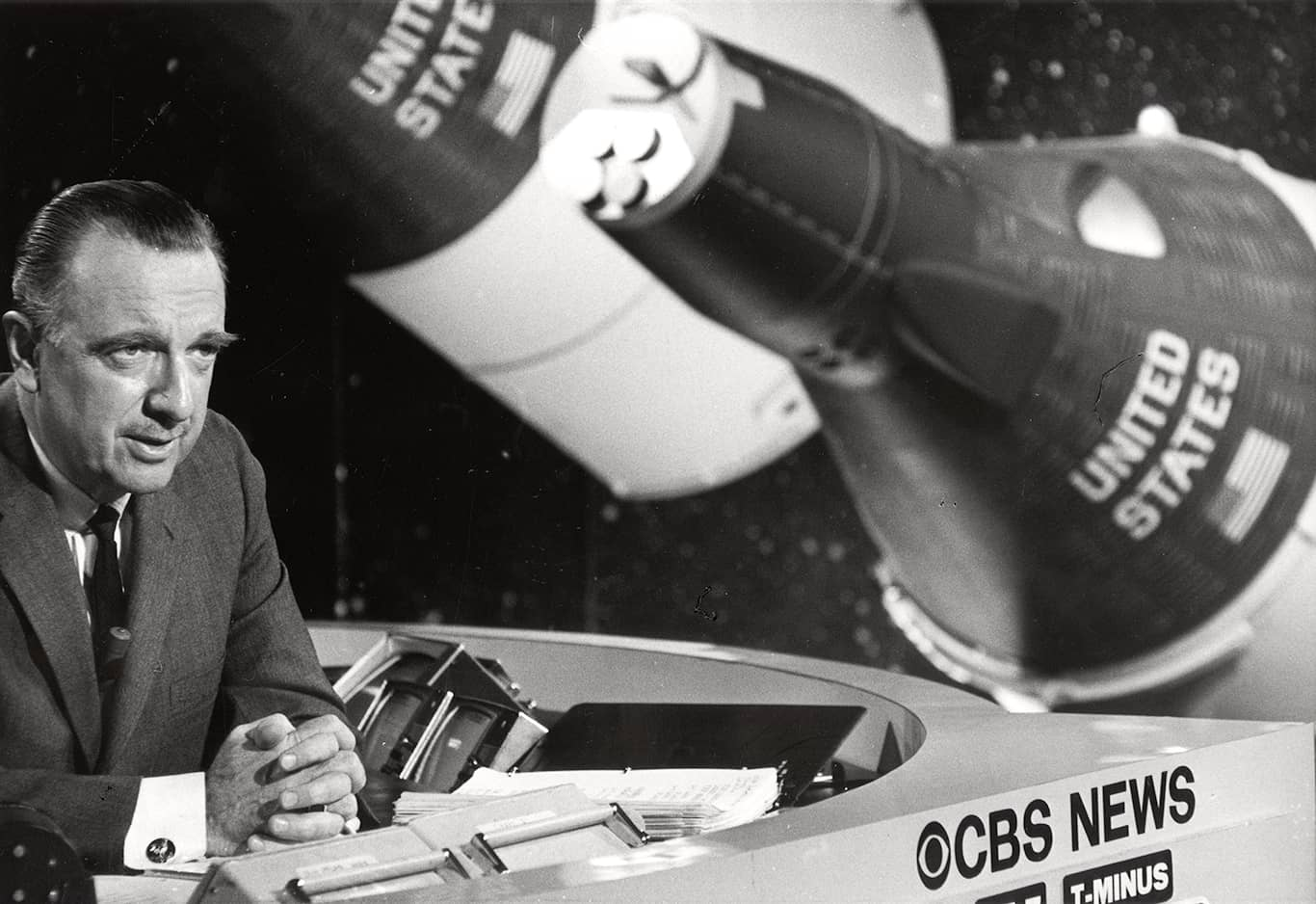 Walter Cronkite at desk and reporting.
