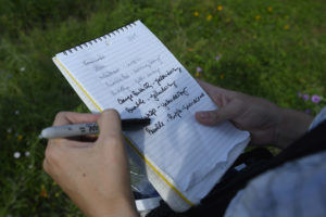 Dr. Susan Cameron Devitt produces a collection vial from her waist pack, harvests the insect, and jots a few words in her notebook.