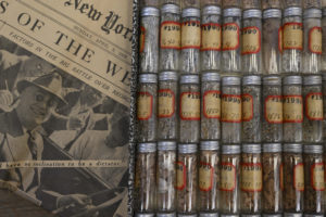 Tiny clear glass vials that show the cuttings, with a newspaper from 1937 with President Franklin D. Roosevelt on the front page.