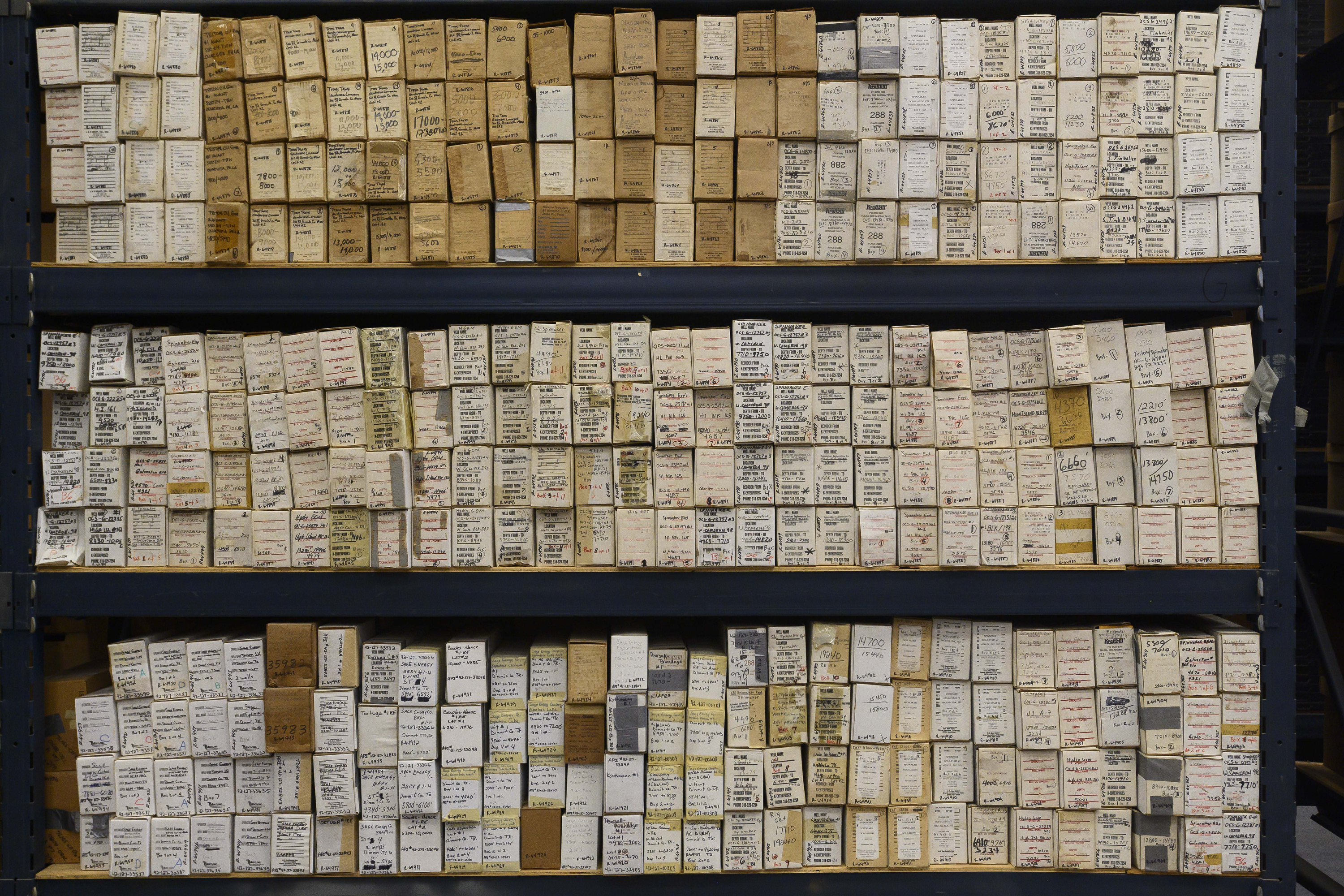 Rows of small brown boxes that contain core samples, all labeled with the location of the well, the date, etc.