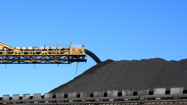 a large yellow conveyor belt carrying coal and emptying onto a huge
