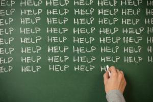 The word help written on a chalk board
