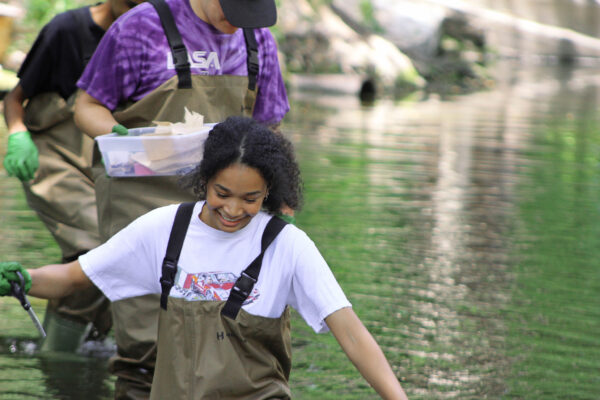Texas high school students walking through creek with specimens.