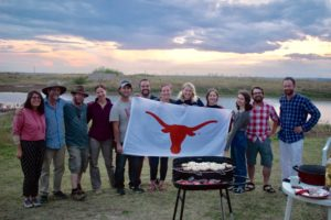 Students holding Longhorn flag at excavation site.