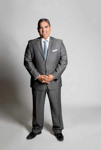 Victor Saenz, professor at UT Austin, poses in front of gray background.