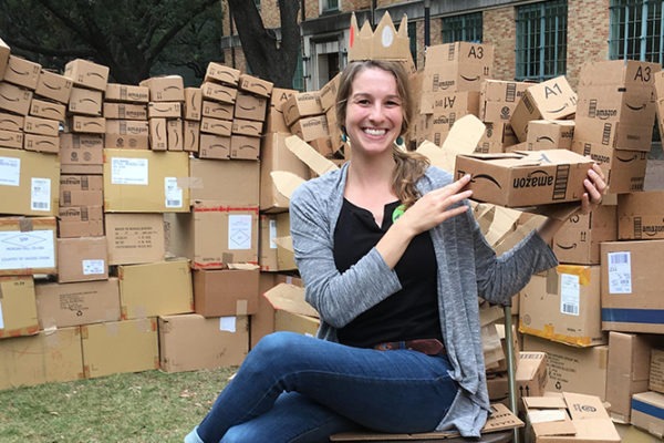 A photo of Brianna Duran surrounded by boxes to be recycled.