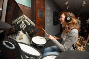 A woman plays a drumkit.