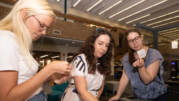 Three women looking at small 3D printed models.