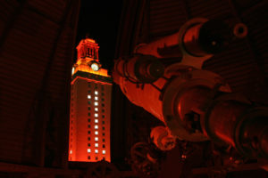 A photo of the Painter telescope and the UT Tower at night.