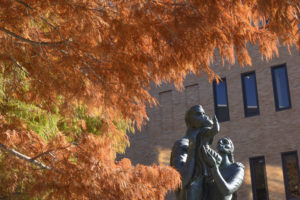The McCombs School Family statue by Charles Umlauf, framed by rust-colored cypress trees.