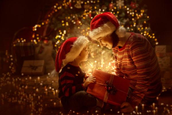 Family open Christmas Lighting Present Gift Box front of Xmas Tree