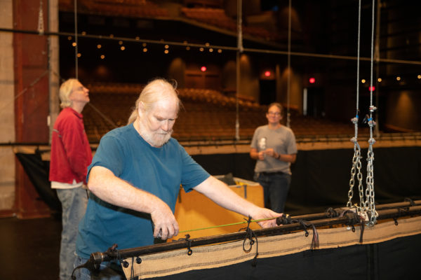 A man uses a measuring tape on a stage as equipment and backdrops are brought in.