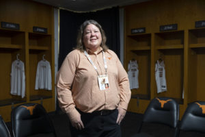 A woman in a burnt orange shirt stands in a locker room.