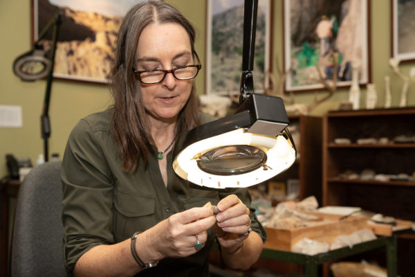 A woman examines a small fossil using a magnifier.