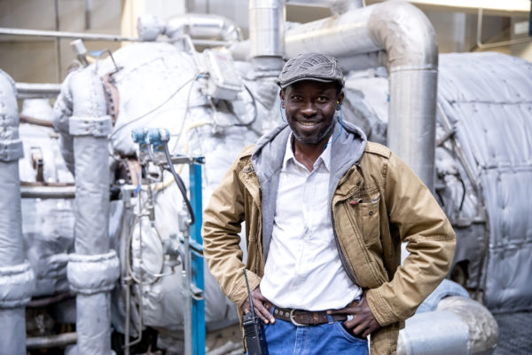 A man stands in front of machinery in a power plant.