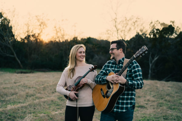 A woman holding a violin and a man holding an acoustic guitar pose together outside in front of a wooded area.