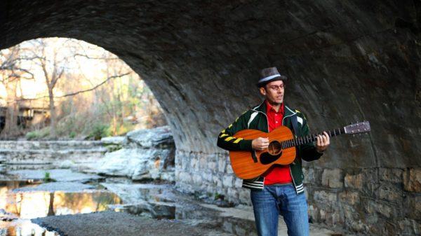 A man plays guitar along a stream under a bridge.