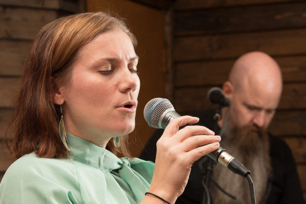 A woman sings into a microphone as a man in the background plays guitar.
