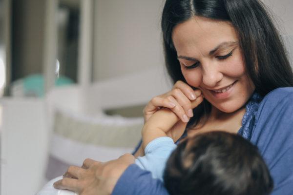 Mother breastfeeding her newborn baby boy