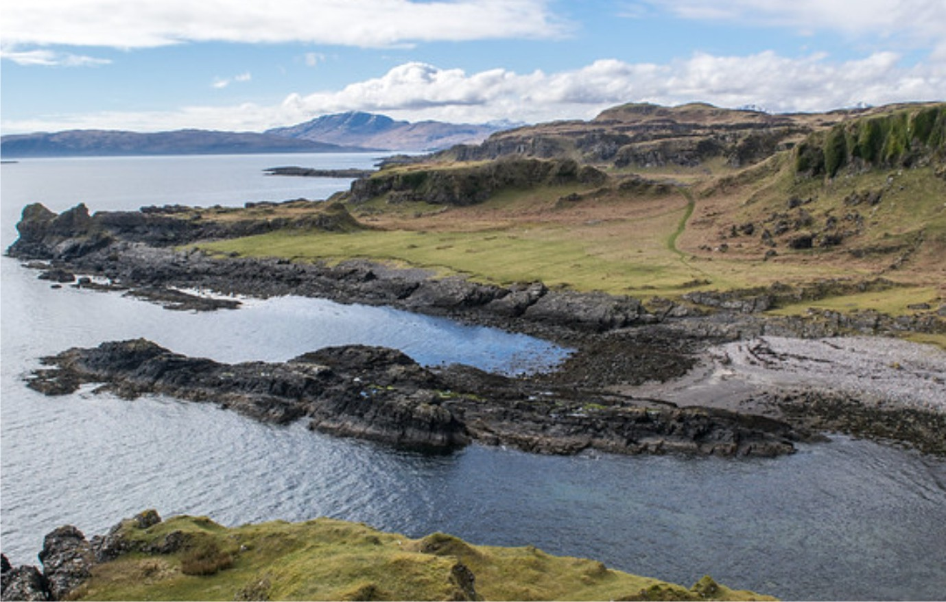 Green grass meets rocky shores and cliffs overlooking the sea on the coast of Kerrera