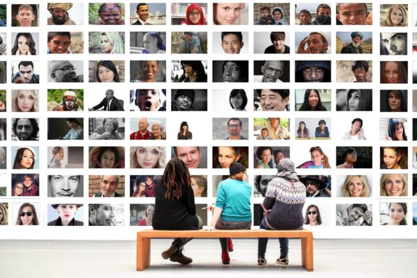 Three people look at a grid of diverse faces.