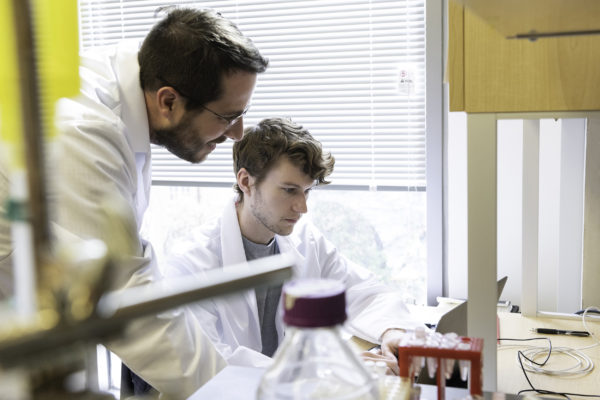 Two men in white lab coats work in a classroom laboratory.
