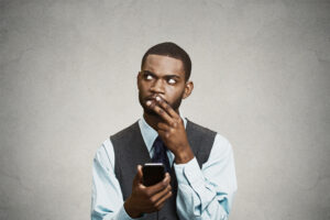 Confused executive thinking reply to message on smart phone